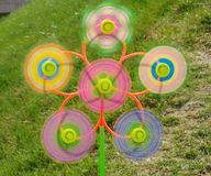 Spinning windmills in the meadow. A toy has six windmills in a green meadow, each windmills is spinning Stock Photography