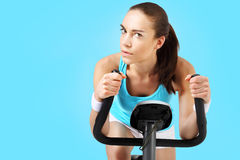 Spinning woman exercising on a stationary bike Royalty Free Stock Photos