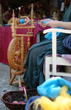 Spinning wool 1. A woman spinning colourful wool on a mandrel Stock Photo
