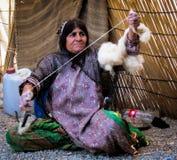 Spinning Wool in rural Iran. Elderly Woman spinning and sorting wool in rural Iran Stock Image