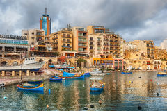 Spinola Bay with bioats in front of famous touristic restaurants. MALTA - JANUARY 23 2015: Spinola Bay with boats in front of famous touristic restaurants and Stock Photo