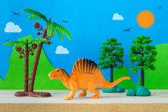 Spinosaurus toy model on wild models background. Closeup Stock Photos