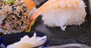 Spinta alta vicina del carrello in considerazione dei un assortimento alimento giapponese: sushi, nigiri, sashimi stock footage