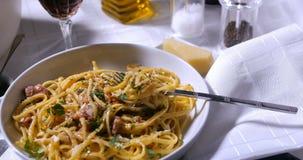 Spinta alta vicina del carrello in considerazione di un piatto del carbonara degli spaghetti stock footage