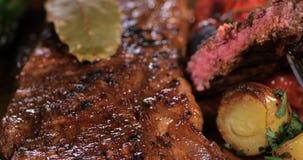 Spinta alta vicina del carrello in considerazione di una bistecca di controfiletto con asparago, le patate ed i pomodori arrostit video d archivio