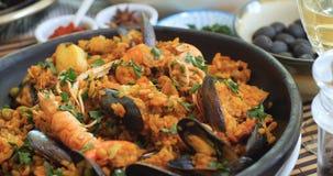 Spinta alta vicina del carrello in considerazione di una paella dei frutti di mare: cozze, gamberetti di re, langoustine, eglefin archivi video