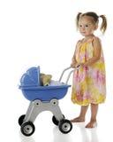 Spinta del bambino in suo carrozzino Immagine Stock