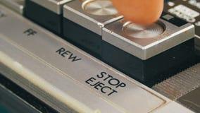 Spinta del tasto di arresto su un registratore d'annata video d archivio