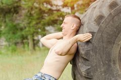 Spinta dell'uomo una grande gomma Allenamento della via Fotografia Stock