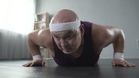 Spinta-UPS di sudore e facente maschio di peso eccessivo adulto per perdere peso, allenamento video d archivio