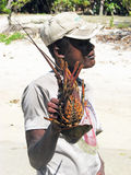 Spiny lobster. Madagascar: a young fisherman is showing a spiny lobster on the beach near the village of Evatra in South of the island. Madagascar's tourist Royalty Free Stock Images