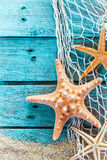 Spiny starfish on turquoise painted boards. Colorful oceanic background with a marine still life of spiny starfish hanging on diamond mesh fish net on weathered Stock Photos