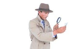 Spion, der durch Vergrößerungsglas schaut Stockfotografie