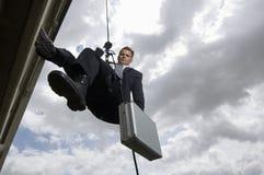 Spion, der mit Koffer Rappelling ist Lizenzfreies Stockfoto