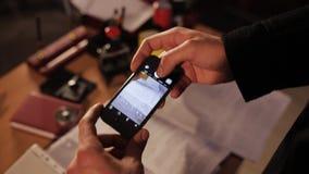 Spion op de telefoon die beelden van geheime dossiers in het bureau nemen stock videobeelden