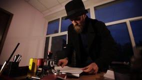 Spion op de telefoon die beelden van geheime dossiers in het bureau nemen stock footage