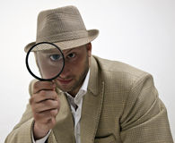 Spionerende mens met vergrootglas Royalty-vrije Stock Afbeeldingen