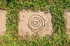 Spiraal op Vierkante Steen als het bedekken met gras stock foto