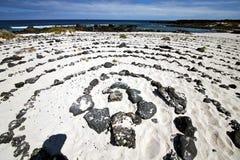 Spiraal van zwarte rotsen in het witte strand   lanzarote Stock Foto