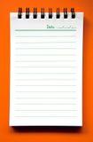 Spiraalvormig notitieboekje op oranje achtergrond Stock Foto's