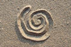 Spiraalvormig teken in zand Stock Foto's