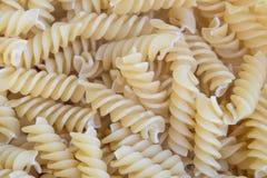 Spiraalvormige ruwe deegwarenachtergrond Stock Foto's