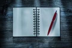 Spiraalvormige zakboekje rode pen op houten raad stock foto's