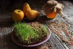 Spirade groddar av vete, honung och päron på en trägammal sprucken yttersida Fotografering för Bildbyråer