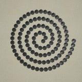 Spiral av grå färgstenen på sand arkivfoton