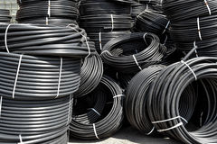 Spiral black plastic pipes, stored in the open air. Background. Coiled plastic pipes stored outdoors Stock Images