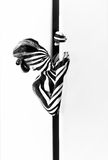 Spiral bodyart on the body of a young girl peeking out. From behind the door. Look like zebra pattern skin Stock Image