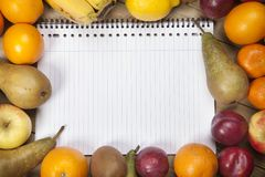 Spiral book amidst fruits. Spiral book amidst variety of fruits on wooden plank Stock Images