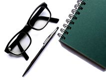Spiral bound notebook, glasses and pen on white ba Stock Photography