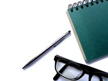 Spiral bound notebook, glasses and pen. On a white background Stock Image