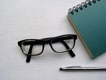 Spiral bound notebook, glasses and pen. On a white painted wood background Stock Images