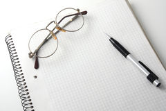 Spiral bound notebook with glasses and pencil Stock Photos