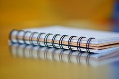 Spiral-bound notebook on a golden and blue background with reflection. Work in the office. Research and training royalty free stock images