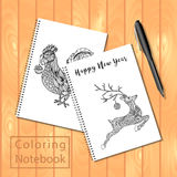 Spiral bound notepads or coloring book with pen and pictures, rooster, jumping deep. Royalty Free Stock Photos