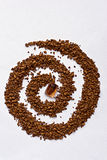 Spiral of coffee with a cane sugar cube on white Royalty Free Stock Photos