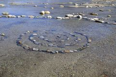 Spiral of composite stones in water, esoteric stones,. Spiral of composite stones in water, on shore of lake como, esoteric stock images
