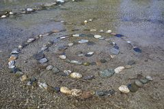 Spiral of composite stones in water, esoteric stones,. Spiral of composite stones in water, on shore of lake como, esoteric royalty free stock image