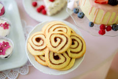 Spiral cookies, cake and cupcakes laid on table. Royalty Free Stock Images