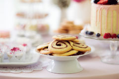 Spiral cookies, cake and cupcakes laid on table. Royalty Free Stock Photography