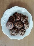 Spiral cookies. Carob spiral cookies in brown tones and in white plate royalty free stock photography