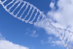 Spiral dna against the blue sky with clouds.  royalty free stock photo