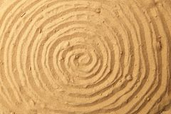 Spiral drawing on beach sand background. Spiral pattern on golden sand. Sand texture Stock Image