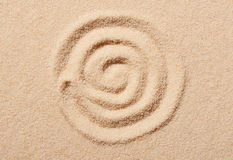 Spiral drawn on beach sand. Summer beach background. View from above Stock Images