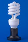 Spiral energy saving bulb on the background. Spiral energy saving bulb on the blue background Royalty Free Stock Photos