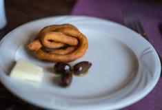 Spiral för svarta oliv, ost- och brödpå en platta Arkivbilder