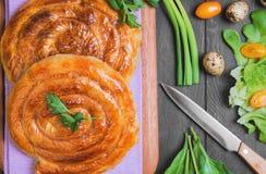 Spiral filo pie. S burek, Greek Bougatsa, lettuce, green onions, parsley, yellow cherry tomatoes, quail eggs in a wooden bowl on a napkin on a dark black Stock Images